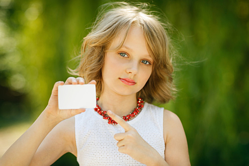Girl showing blank credit card and pointing at it